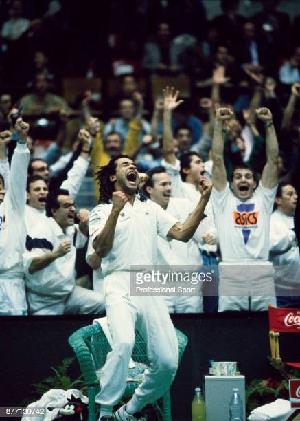 Team captain Yannick Noah celebrates with his teammates after France defeats the USA in the Davis Cup Final at Palais des Sports de Gerland in Lyon...