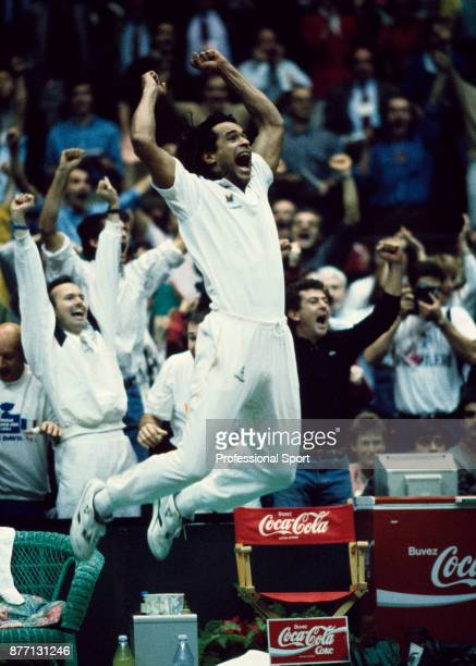 Team captain Yannick Noah jumps in celebration with his teammates after France defeats the USA in the Davis Cup Final at Palais des Sports de Gerland...