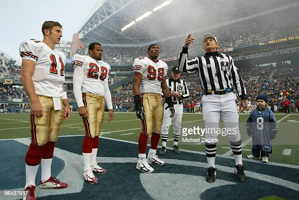Team captains Alex Smith Keith Lewis and Julian Peterson of the San Francisco 49ers look on the coin flip by referee Ed Hochuli before the game...