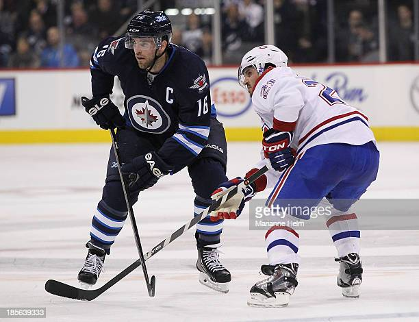 Team captains Andrew Ladd of the Winnipeg Jets and Brian Gionta of the Montreal Canadiens pair up for a faceoff during second period action in an NHL...