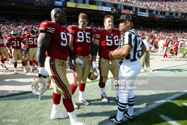 Team captains Bryant Young Jeff Ulbrich and Brock Gutierrez of the San Francisco 49ers meet head linesman John McGrath before the game against the...