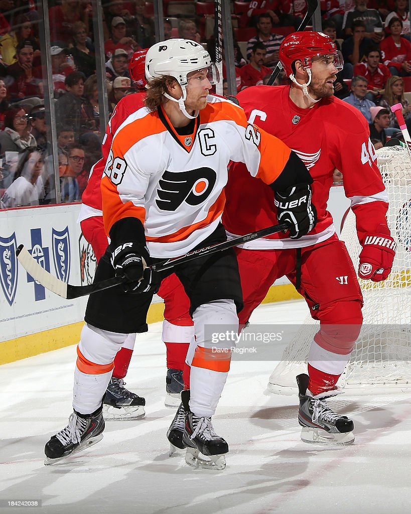 Team captains <a gi-track='captionPersonalityLinkClicked' href=/galleries/search?phrase=Claude+Giroux&family=editorial&specificpeople=537961 ng-click='$event.stopPropagation()'>Claude Giroux</a> #28 of the Philadelphia Flyers and <a gi-track='captionPersonalityLinkClicked' href=/galleries/search?phrase=Henrik+Zetterberg&family=editorial&specificpeople=201520 ng-click='$event.stopPropagation()'>Henrik Zetterberg</a> #40 of the Detroit Red Wings tie on the side of the net during a NHL game at Joe Louis Arena on October 12, 2013 in Detroit, Michigan.