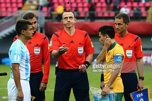 Team captains Lucas Ferraz Vila of Argentina and Joe Caletti of Australia watch referee Ruddy Bouquet toss the coin prior to the FIFA U17 World Cup...