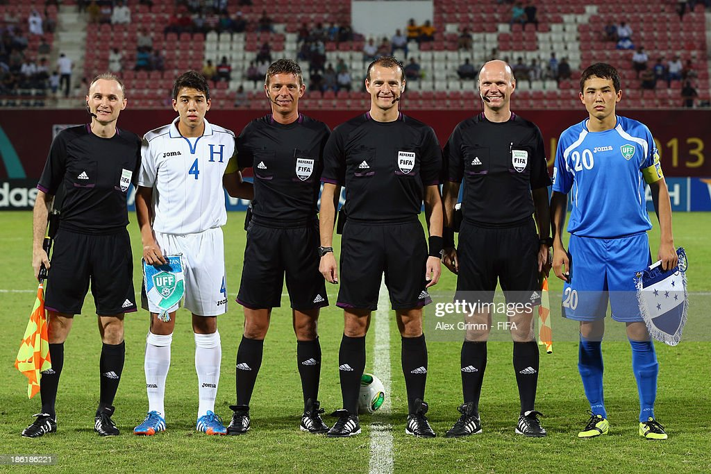 Team captains Luis Santos (2L) of Honduras and Otabek Shukurov of Uzbekistan pose with the match officials prior to the FIFA U-17 World Cup UAE 2013 Round of 16 match between Honduras and Uzbekistan at Sharjah Stadium on October 28, 2013 in Sharjah, United Arab Emirates.