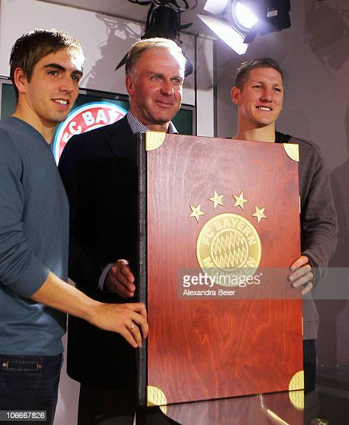 Team captains Philipp Lahm and Bastian Schweinsteiger and CEO of Bayern Muenchen KarlHeinz Rummenigge of Bayern Muenchen present the club's chronicle...