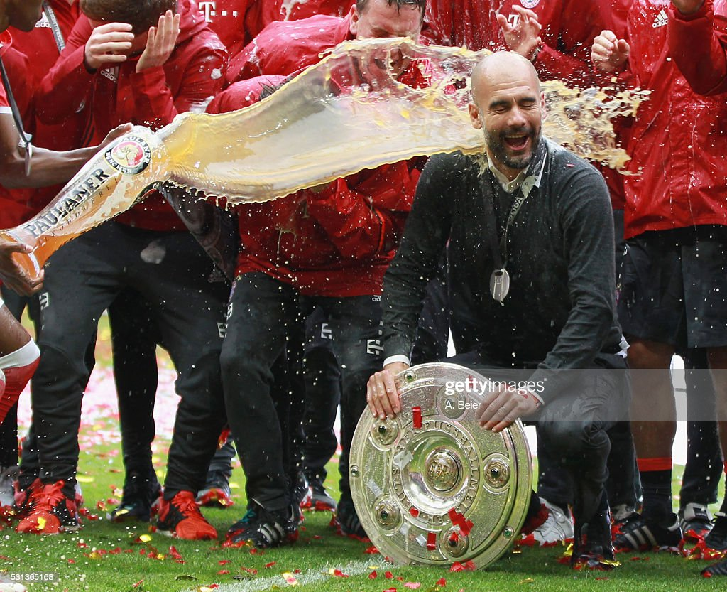 Team coach Josep Guardiola of Bayern Muenchen receives a beer shower from David Alaba during the German Championship celebration after the Bundesliga match between FC Bayern Muenchen and Hannover 96 at Allianz Arena on May 14, 2016 in Munich, Germany.
