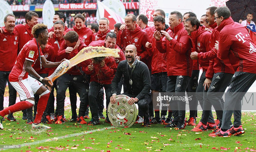 Team coach Josep Guardiola (C) of Bayern Muenchen receives a beer shower from David Alaba (L) during the German Championship celebration after the Bundesliga match between FC Bayern Muenchen and Hannover 96 at Allianz Arena on May 14, 2016 in Munich, Germany.