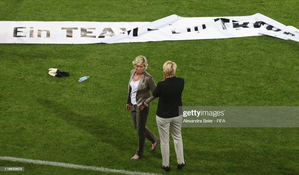 Team coach Silvia Neid (L) of Germany nd manager Doris Fitschen chat after their team's loss next to a banner reading 'One team - a dream' in the FIFA Women's World Cup quarter finals match between Germany and Japan on July 9, 2011 in Wolfsburg, Germany.