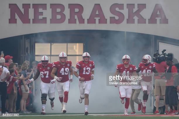 Team cocaptains Jerald Foster and Chris Weber and Tanner Lee and Luke McNitt and Josh Kalu of the Nebraska Cornhuskers enter the field before the...