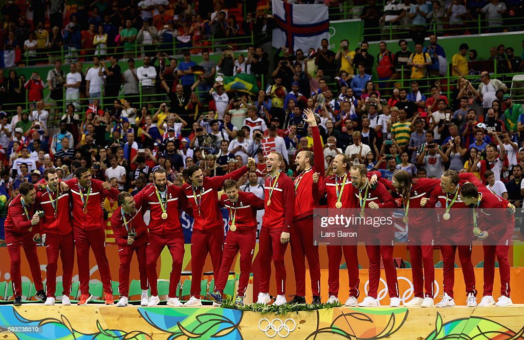 Team Denmark react on the podium during the medal ceremony for Men's Handball after winning the gold medal on Day 16 of the Rio 2016 Olympic Games at...