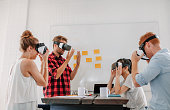 Business people using virtual reality goggles in meeting in office. Team of developers testing virtual reality headset.