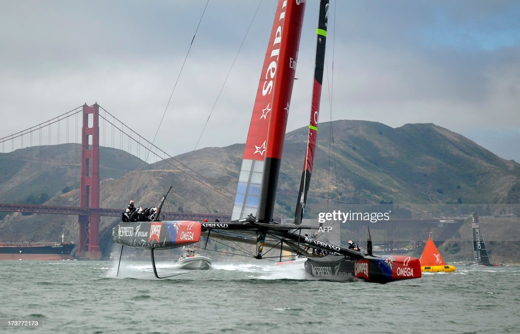Team Emirates New Zealand (L), and Team Oracle USA (R) sail their AC-72 Racing Yachts near the Golden Gate Bridge during a training session for the America's Cup race in San Francisco, California on July 17, 2013. Oracle Team USA is not yet allowed to train on the official course as they have not yet met all of the mandated safety requirements for the competition. AFP PHOTO/Josh EDELSON