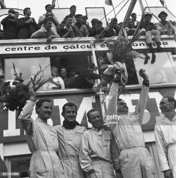 Team Ferrari motor racing drivers Ludovico Scarfiotti and Lorenzo Bandini celebrate their victory at 1963 24 Hours of Le Mans alongside British...