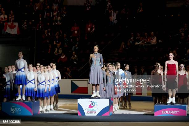 Team Finland Marigold IceUnity Team Russia Paradise and Team Canada Nexxice stand for the National Anthem of Russis at the medal ceremony during the...