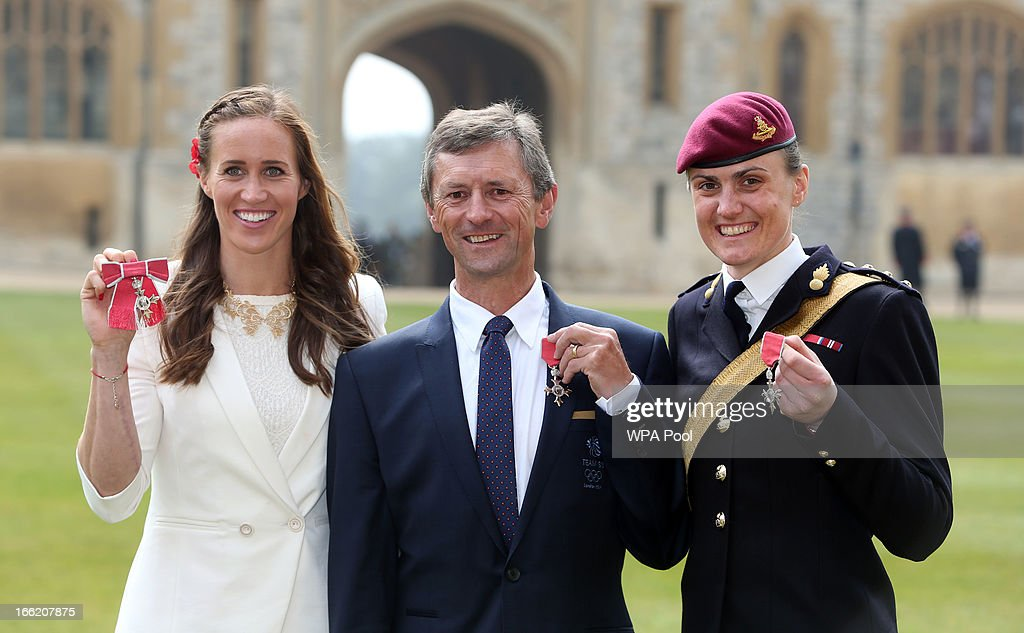 Team GB rowers Helen Glover (R) and Captain Heather Stanning (L) with with coach Robin Williams pose with their MBE's at an Investiture ceremony at Windsor Castle on April 10, 2013 in Windsor, England.