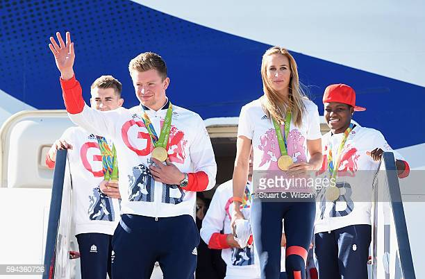 Team GB Swimmer and gold medallist Adam Peaty waves as he leaves the aeroplane with fellow gold medallist and rower Helen Glover after arriving home...