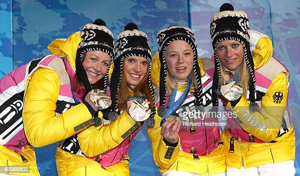 Team Germany celebrates receiving the silver medal during the medal ceremony for the ladies' 4x5 km crosscountry skiing relay on day 14 of the...