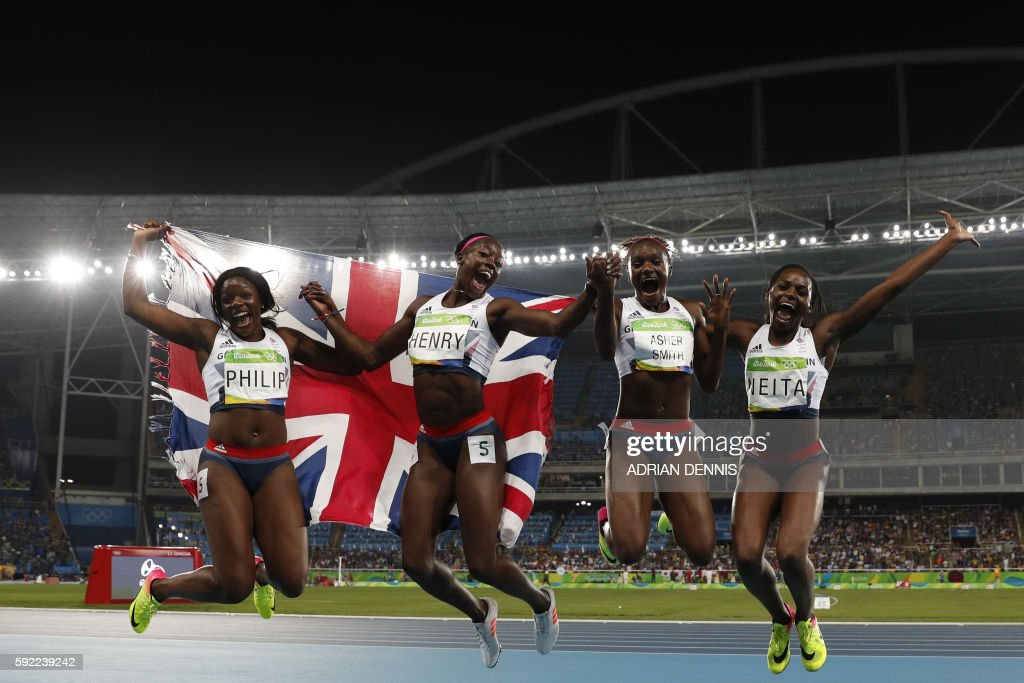 TOPSHOT - Team Great Britain (LtoR) Great Britain's Asha Philip, , Great Britain's Desiree Henry Britain's Dina Asher-Smith and Great Britain's Daryll Neita celebrate after finishing third of the Women's 4x100m Relay Final during the athletics event at the Rio 2016 Olympic Games at the Olympic Stadium in Rio de Janeiro on August 19, 2016. / AFP / Adrian DENNIS
