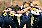 Fastpitch Softball team huddle before the start of a softball game.  Photo is in color.  All logos have been removed.