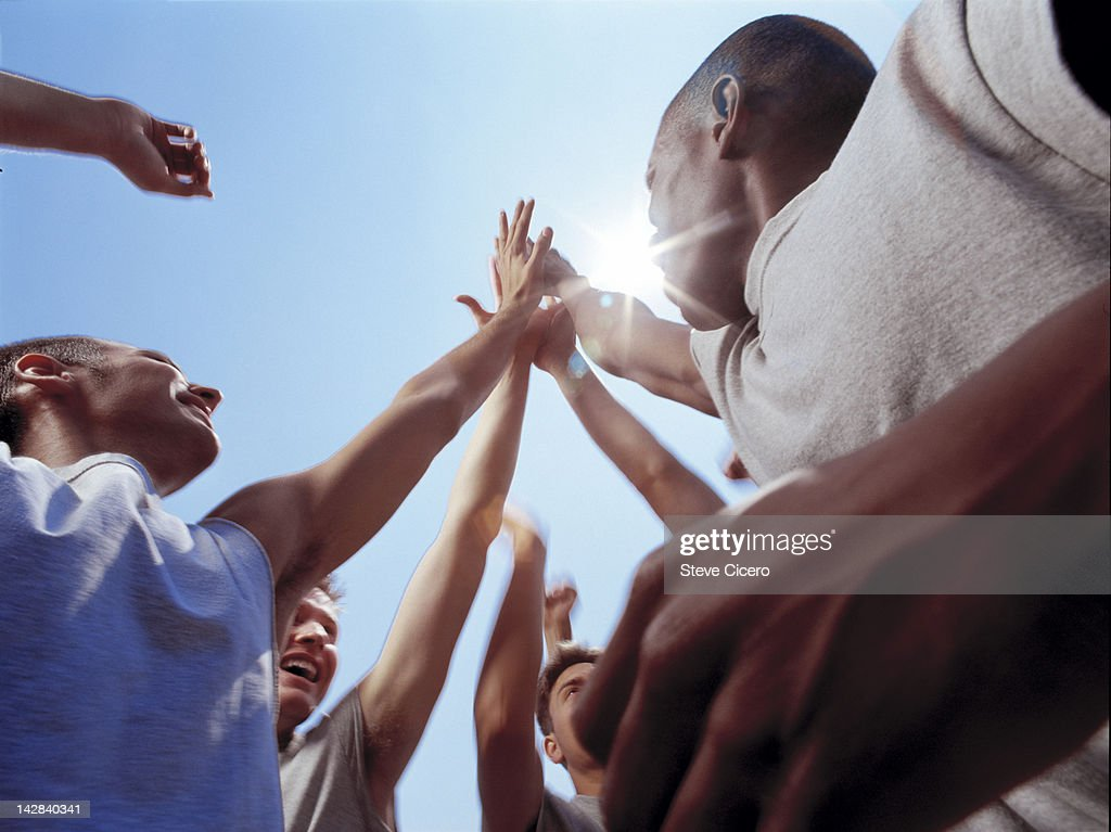 A team huddle with arms stretched out : Stock Photo