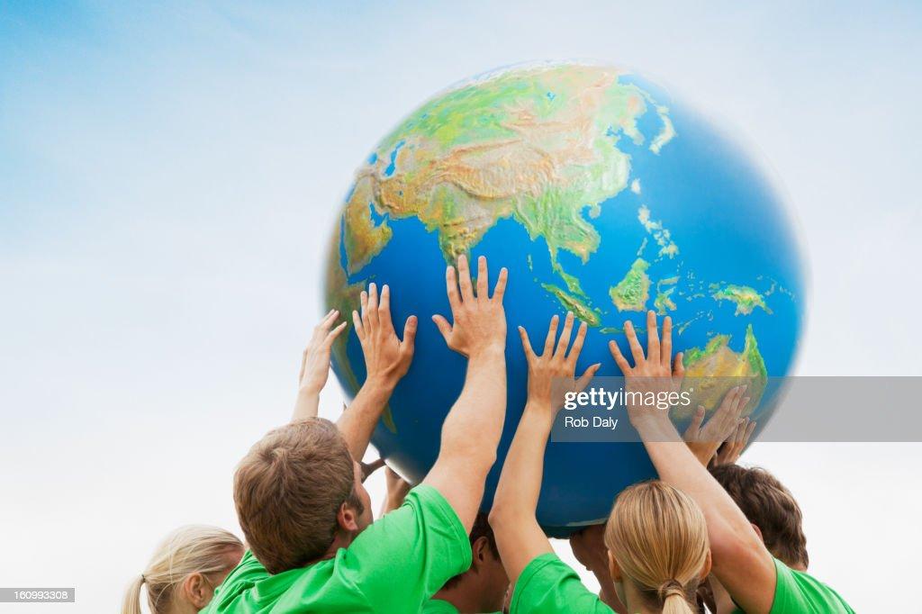 Team in green t-shirts lifting globe overhead : Stock Photo