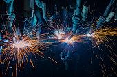 Team industrial robots are welding car part