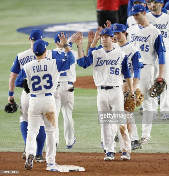 Team Israel players exchange highfives after their 41 victory over Cuba in a Pool E secondround World Baseball Classic match at Tokyo Dome on March...