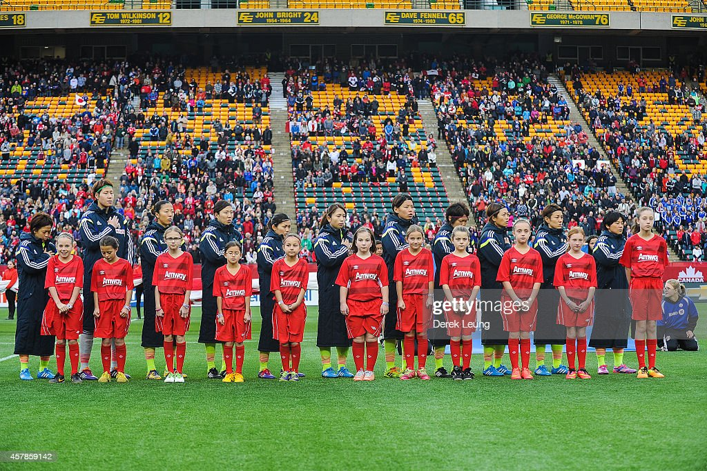 Team Japan lines up with kids during the singing of their national anthem prior to a match against Canada at Commonwealth Stadium on October 25, 2014 in Edmonton, Alberta, Canada.