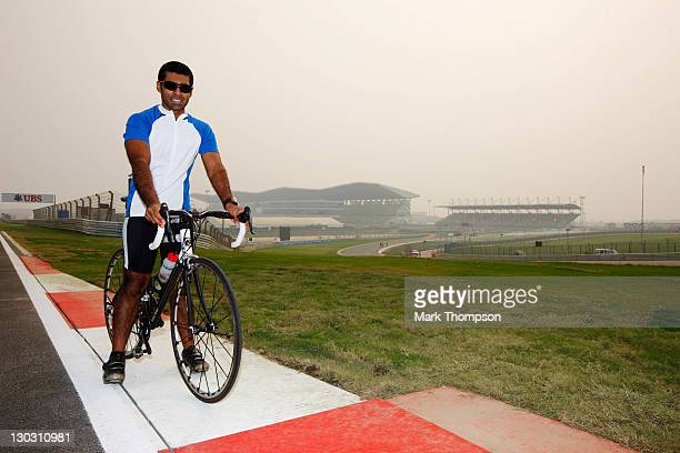 Team Lotus reserve driver Karun Chandhok of India cycles the track as preparations continue during previews to the Indian Formula One Grand Prix at...