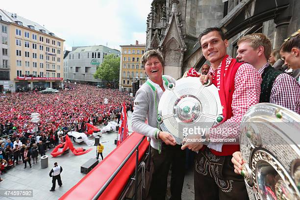 Team manager Karin Danner of Bayern Muenchen poses with head coach Thomas Woerle and the German Championship winners trophy as the team celebrate...
