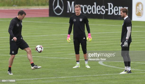 Team manager of the German national soccer team Oliver Bierhoff kicks with goalkeepers Bernd Leno and Kevin Trapp during a training session on June 9...