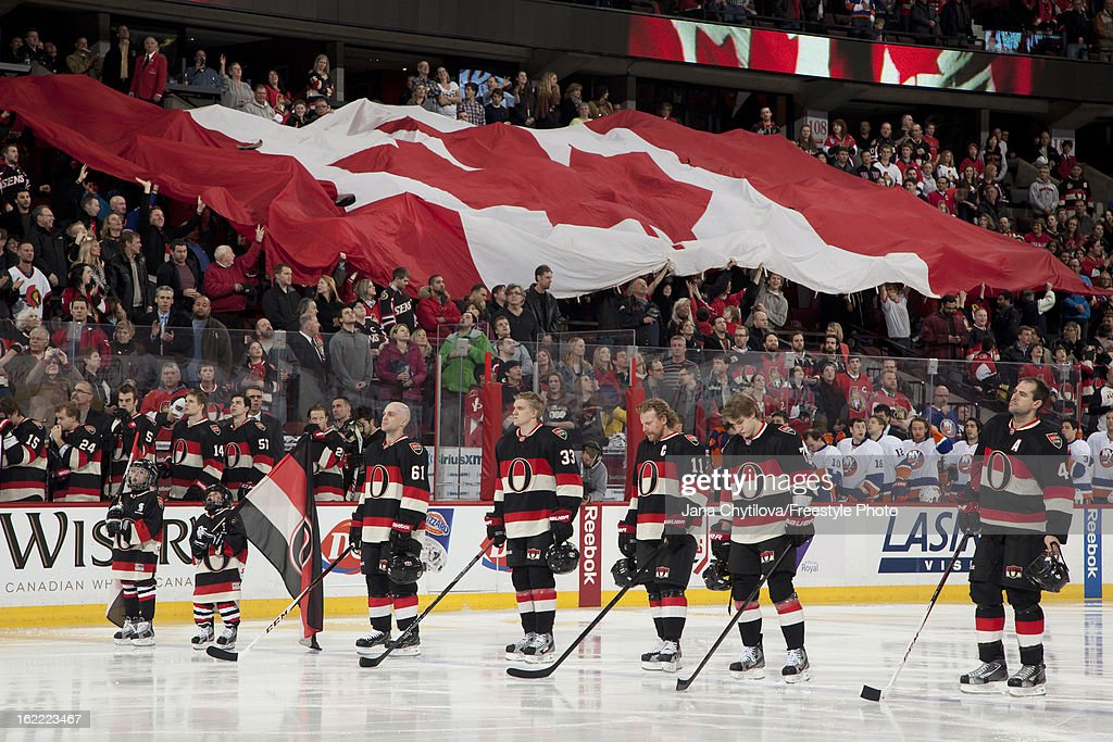 Team mates Andre Benoit #61, Jakob Silfverberg #33, Daniel Alfredsson #11, Kyle Turris #7, and Chris Phillips #4 of the Ottawa Senators stand as a large Canadian flag is passed amongst the fans, during the singing of the national anthems prior to an NHL game against the New York Islanders at Scotiabank Place on February 19, 2013 in Ottawa, Ontario, Canada.