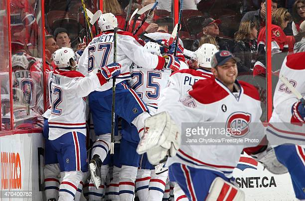 Team mates Brian Flynn Max Pacioretty and Jacob De La Rose of the Montreal Canadiens celebrate their overtime win against the Ottawa Senators in Game...