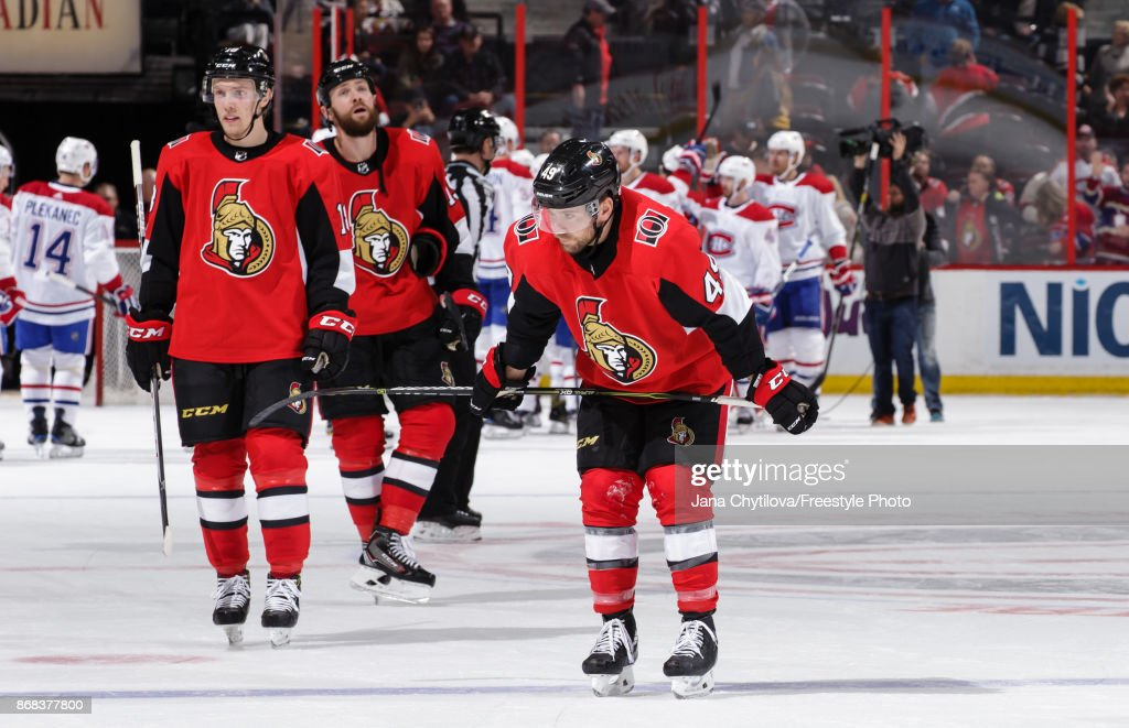 Team mates Christopher DiDomenico #49, Ryan Dzingel #18 and Zack Smith #15 of the Ottawa Senators react as members of the Montreal Canadiens celebrate their win at Canadian Tire Centre on October 30, 2017 in Ottawa, Ontario, Canada.
