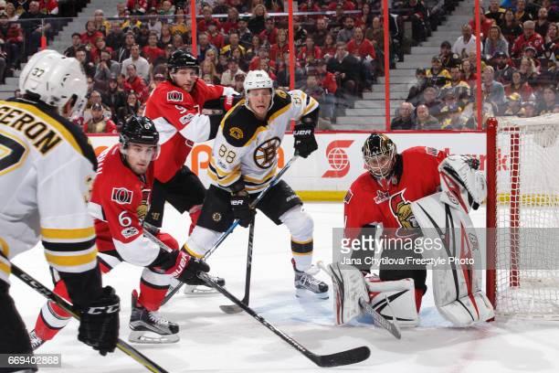 team mates Craig Anderson Bobby Ryan and Chris Wideman of the Ottawa Senators defend against David Pastrnak and Patrice Bergeron of the Boston Bruins...