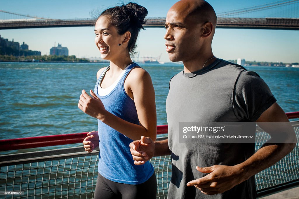 Team mates running along waterfront, New York, USA