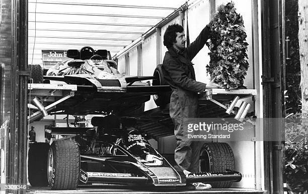 A team mechanic loading American racing driver Mario Andretti's winning laurels into the team trailer after his victory in the French Grand Prix