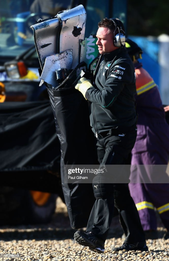 A team mechanic removes the wreckage of the W04 car belonging to Lewis Hamilton of Great Britain and Mercedes GP after crashing into the gravel at turn six after crashing during Formula One winter testing at Circuito de Jerez on February 6, 2013 in Jerez de la Frontera, Spain.