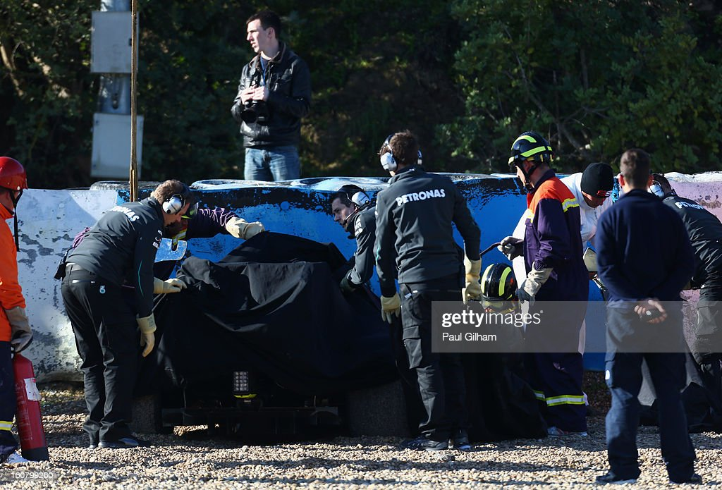 Team mechanics remove the wreckage of the W04 car belonging to Lewis Hamilton of Great Britain and Mercedes GP after crashing into the gravel at turn six after crashing during Formula One winter testing at Circuito de Jerez on February 6, 2013 in Jerez de la Frontera, Spain.