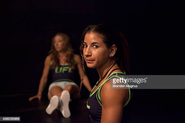 Team Melendez fighters Tecia Torres and Heather Jo Clark wait to watch teammate Lisa Ellis fight team Pettis fighter Jessica Penne during filming of...