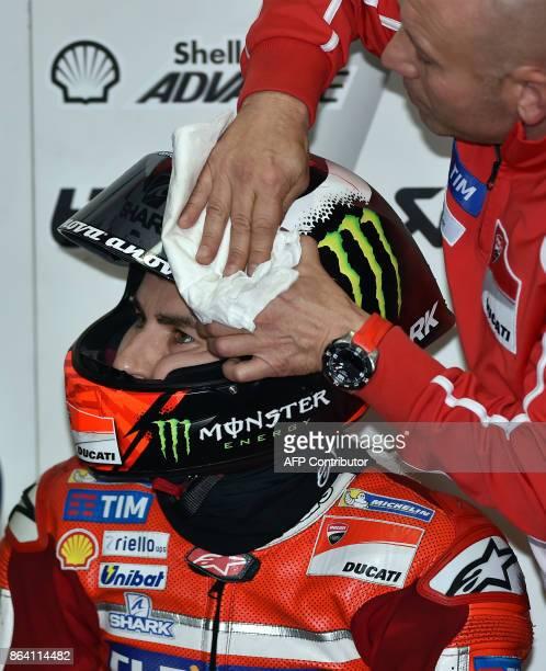 A team member cleans Ducati rider Jorge Lorenzo of Spain's helmet visor during the third practice session of the Australian MotoGP Grand Prix at...