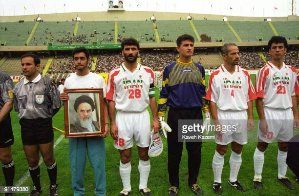 A team member of the Iran national football team holds a portrait of Ayatollah Khomeini during a match against a foreign team at Azadi Stadium Tehran...