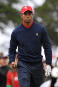 US Team member Tiger Woods reacts to his shot from the third tee during the final round singles matches at the Presidents Cup golf competition on...