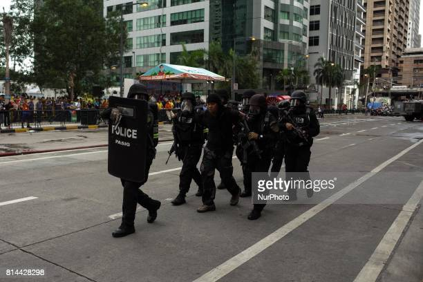 SWAT team members escort a mock suspect of a terrorist attack during an antiterrorism drill in Pasig City east of Manila Philippines on Friday July...