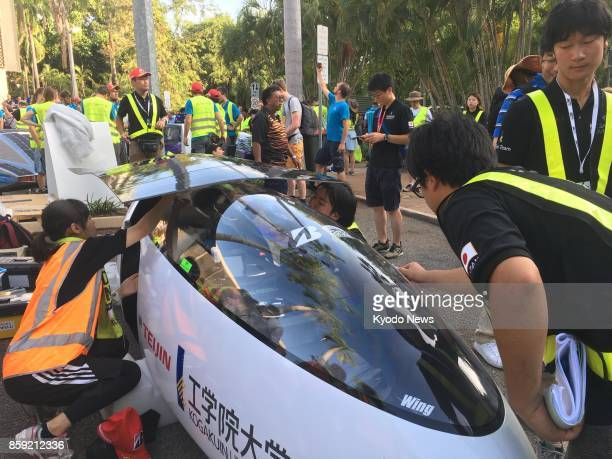 Team members from Kogakuin University perform final checks on its solar car named 'Wing' in Darwin on Oct 8 before starting a 3000kilometer endurance...