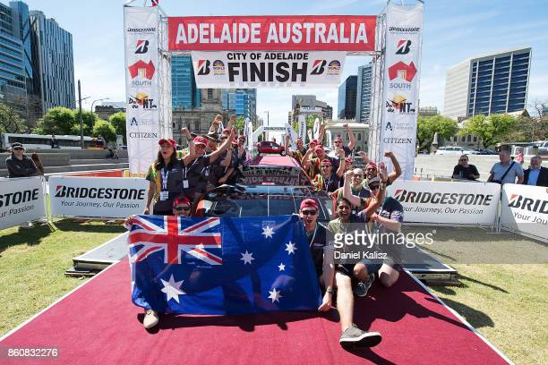 Team members of Clenergy Team Arrow vehicle 'Arrow STF' from Australia celebrate at the finish line on Day 6 of the 2017 Bridgestone World Solar...