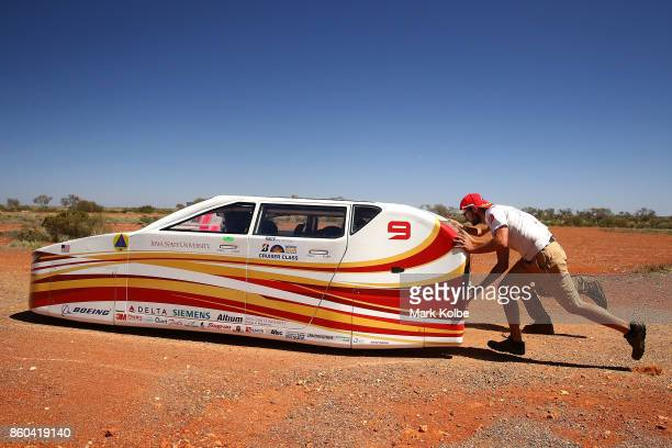 Team members of PrISUm from the United States of America push their vehicle 'Penumbra' back up to the Stuart Highway after a break from racing in the...