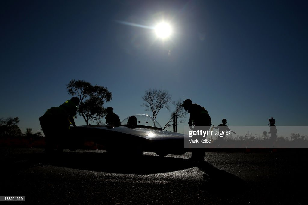 Team members of Tokai Challenger from Tokai University in Japan move their car into position on the road to start racing on Day 3 on October 8, 2013 outside of Ti Tree, Australia. Over 25 teams from across the globe are competing in the 2013 World Solar Challenge - a 3000 km solar-powered vehicle race between Darwin and Adelaide. The race began on October 6th with the first car expected to cross the finish line on October 10th.
