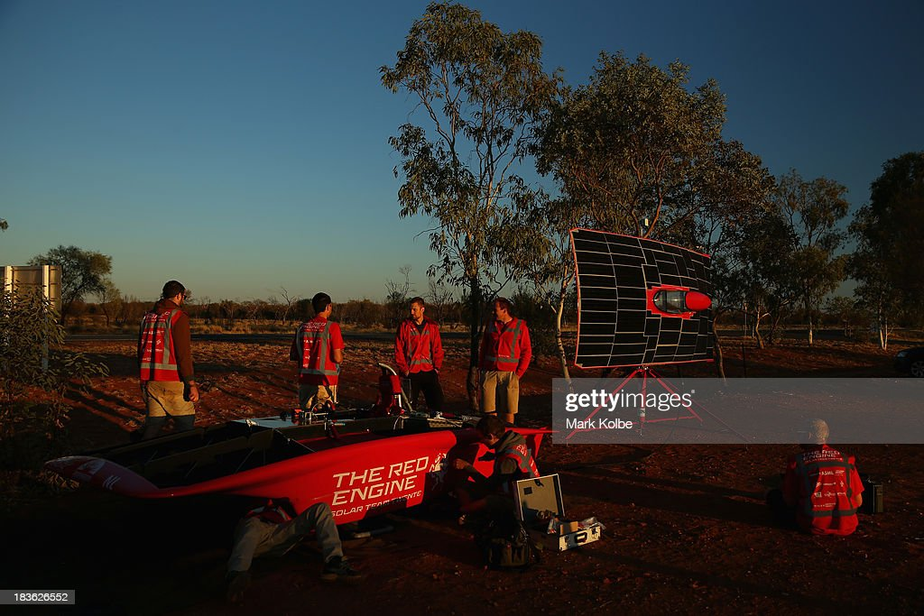 Team members prepare the RED Engine from the Solar Team Twente, University of Twente and Saxion in the Netherlands at sunrise as they prepare for the start of racing on Day 3 on October 8, 2013 outside of Ti Tree, Australia. Over 25 teams from across the globe are competing in the 2013 World Solar Challenge - a 3000 km solar-powered vehicle race between Darwin and Adelaide. The race began on October 6th with the first car expected to cross the finish line on October 10th.