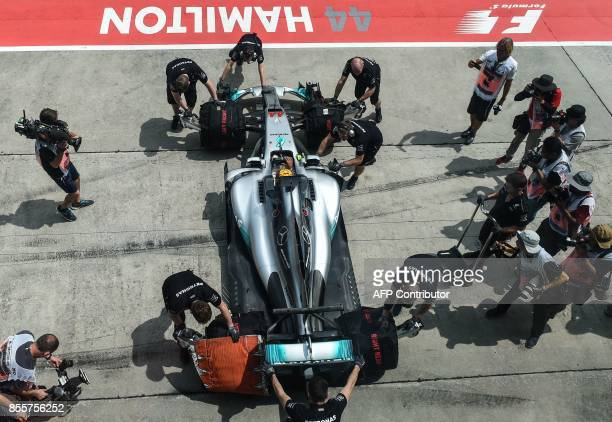 Team members push Mercedes' British driver Lewis Hamilton's car back to the garage during the third practice session of the Formula One Malaysia...
